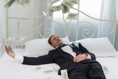 Young Businessman with happy, smile on the bed. who are successf. Ul in business and many banknote dollars money. business success concept Stock Image
