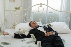 Young Businessman with happy, smile on the bed. who are successf. Ul in business and many banknote dollars money. business success concept stock photo