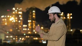 Young businessman in hardhat dancing in front of oil and gas factory. Victory dance.