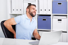 Young businessman has backache at work with a laptop