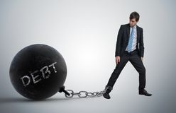 Young businessman has chained big metal ball to his leg with debt written. Young businessman has chained big metal ball to his leg with debt written stock images