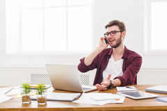 Young businessman has a mobile talk in modern white office. Young businessman in casual has mobile phone talk in modern white office interior Stock Photography