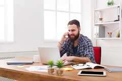 Young businessman has a mobile talk in modern white office Stock Photography