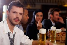 Young businessman having beer in pub Royalty Free Stock Photos