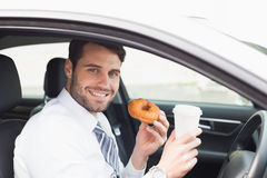 Young businessman having coffee and doughnut Royalty Free Stock Photos