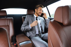 Young businessman having a coffee in his car Royalty Free Stock Image