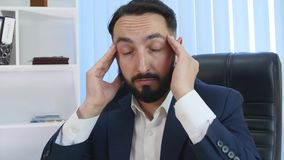 Young businessman having head pain during work in office. By night stock video