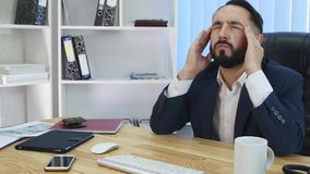 Young businessman having head pain during work in office. By night stock video footage