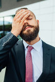 Young businessman having headache because of problems at work. Young businessman having headache because of problems at work stock photography