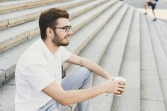 Young businessman having rest with coffee outdoors. Pensive businessman having rest outdoors. Young serene salesman sitting on stairs with take away coffee, copy Royalty Free Stock Image