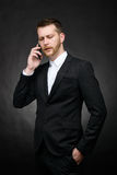 Young businessman having a serious conversation on smartphone Royalty Free Stock Image