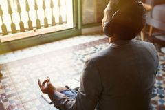 Young businessman in headphones meditating in lotus pose taking a deep breath at home.Business yoga and stress free. Environment.Peace of mind concept.Blurred stock photos