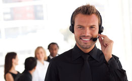 Young Businessman on headset. In office environment Royalty Free Stock Photography