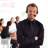 Young Businessman on headset. Young Businessman talking on a headset in office environment Royalty Free Stock Images