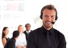 Young Businessman with a headset on. In office environment Royalty Free Stock Photos