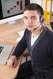 Young businessman with headset on in the office Stock Photography