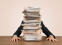 Young businessman hid behind with stack of papers. Business man stack businessman papers young adult money royalty free stock images