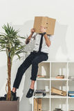 Young businessman hiding face with folder while sitting on bookshelf Royalty Free Stock Images