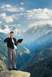 Young businessman with his laptop talking by phone on the mounta Stock Photos