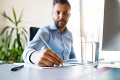 Young businessman in his office writing something with pencil. Stock Photos