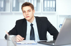 Young businessman at his workplace. Portrait of young serious businessman at his workplace in bright office Royalty Free Stock Image