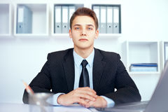 Young businessman at his workplace. Portrait of young serious businessman at his workplace in bright office Stock Photo