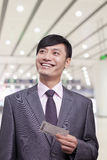 Young businessman holding airplane ticket, Beijing Royalty Free Stock Image
