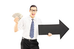 Young businessman holding an arrow pointing to the right and dol Royalty Free Stock Image