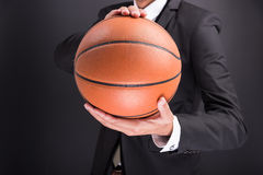 Young businessman holding basketball ball Royalty Free Stock Images