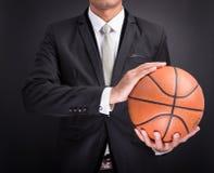 Young businessman holding basketball ball Stock Image
