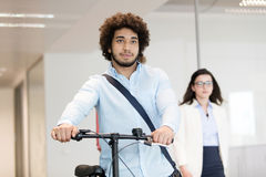 Young businessman holding bicycle with female colleague in background at office Stock Photo