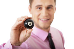 Young businessman holding billiard ball. Stock Image