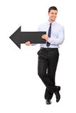 Young businessman holding black arrow pointing right Stock Photo