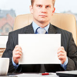 Young businessman holding blank. Portrait of a young businessman holding blank paper stock images
