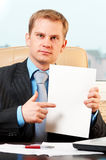Young businessman holding blank pape. Portrait of a young businessman holding blank paper royalty free stock photo