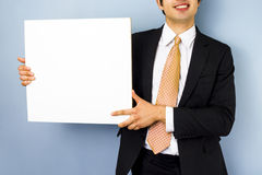 Young businessman holding blank sign. Smiling young businessman holding blank sign Stock Images
