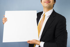 Young businessman holding blank sign. Young smiling businessman holding blank sign Royalty Free Stock Photos