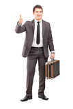 Young businessman holding a briefcase and giving thumb up Royalty Free Stock Photography