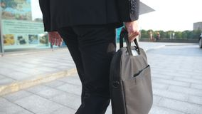 Young businessman holding briefcase in hand and walking in city. Business man commuting to work. Confident guy in suit. Being on his way to office building stock video