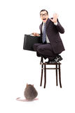 Young businessman holding briefcase standing on chair terrified. Terrified businessman holding briefcase standing on a chair and screaming isolated on white Royalty Free Stock Photo