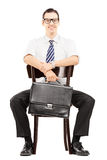 Young businessman holding a briefcase and waiting on a chair Stock Photo