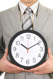 Young businessman holding a clock Royalty Free Stock Photography