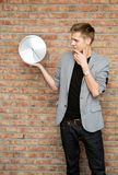 Young businessman holding a clock on brick wall background. Stock Images