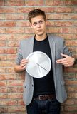 Young businessman holding a clock on brick wall background. Stock Photos