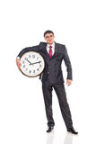Young businessman holding a clock Stock Photo