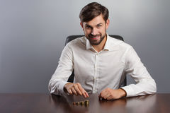 Young businessman holding a coin with row stacks Stock Photos