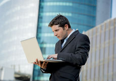 Young businessman holding computer laptop working urban business outdoors Stock Images