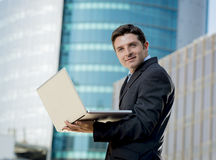 Young businessman holding computer laptop working urban business outdoors Royalty Free Stock Image