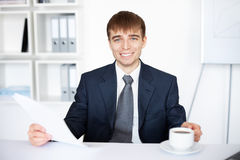 Young businessman holding cup of coffee in office. Portrait of young businessman holding a cup of coffee and papers at the office Stock Photo