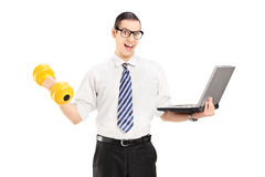 Young businessman holding dumbbell and laptop Stock Photo